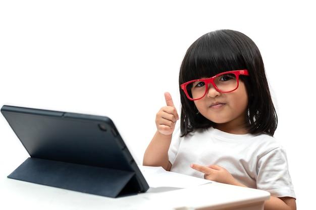 Klein aziatisch kleutermeisje met een rode bril en met behulp van tablet-pc en duimen omhoog