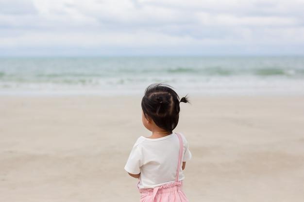 Klein aziatisch meisje dat naar de zee kijkt