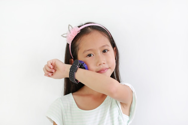 Klein aziatisch meisje dat slimme horloge gebruikt tegen een witte achtergrond. kind spreek en luister naar het slimme horloge uit zijn hand