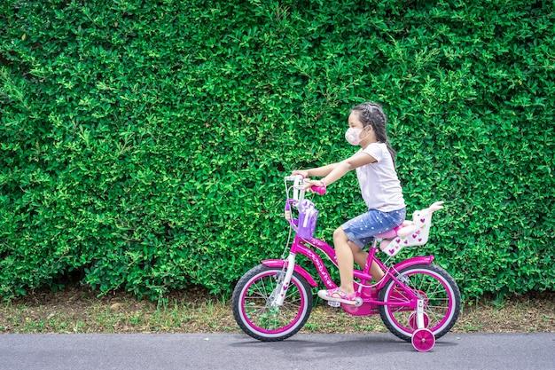 Klein aziatisch meisje draagt een masker tegen pm 2.5 luchtvervuiling of coronavirus tijdens het fietsen