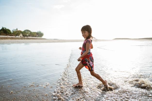 Klein aziatisch meisje draait op de kust