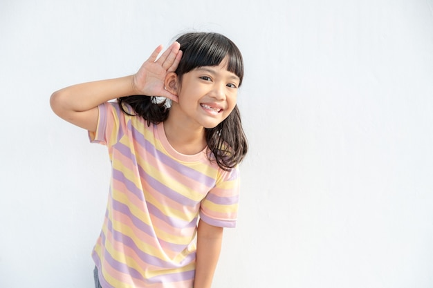 Klein aziatisch meisje houdt haar hand bij haar oor en luistert. handicap dag. dove jongen. opwindend gezicht op aziatisch kindmeisje. de telefoon uitzetten en naar je kind luisteren.