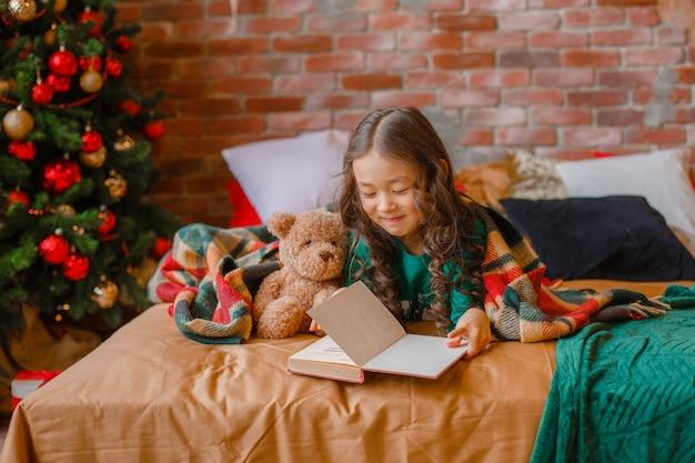 Klein aziatisch meisje in pyjama in de slaapkamer liggend op bed bij de kerstboom die een boek leest