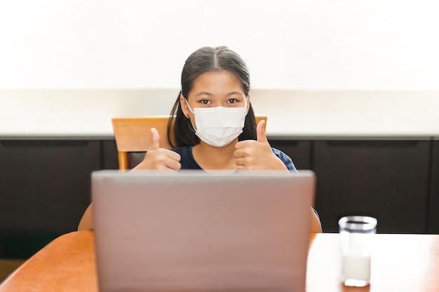Klein aziatisch meisje met gezichtsmasker met duim omhoog studeert thuis met laptop.