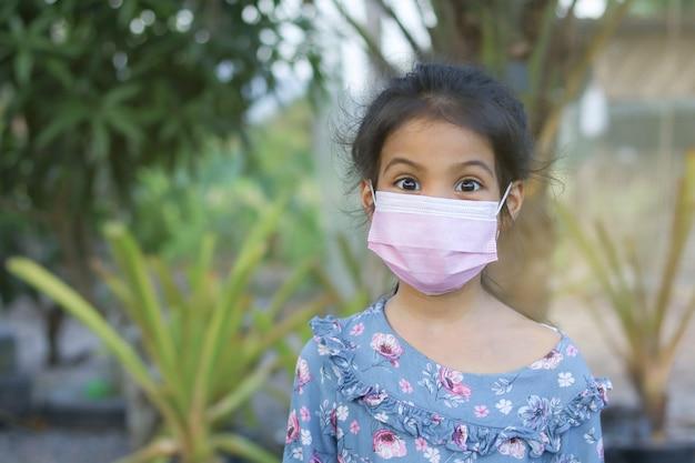 Klein aziatisch meisje met gezichtsmasker voor covid-19