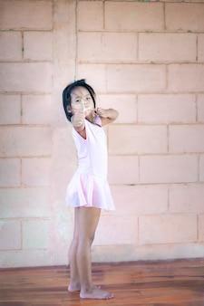 Klein aziatisch meisje schieten houten katapult tegen muur achtergrond, actieve recreatie voor kinderen.