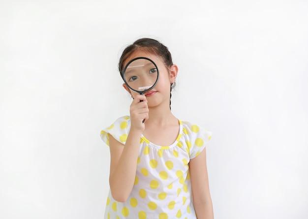 Klein aziatisch meisjeskind dat door vergrootglas op witte achtergrond kijkt