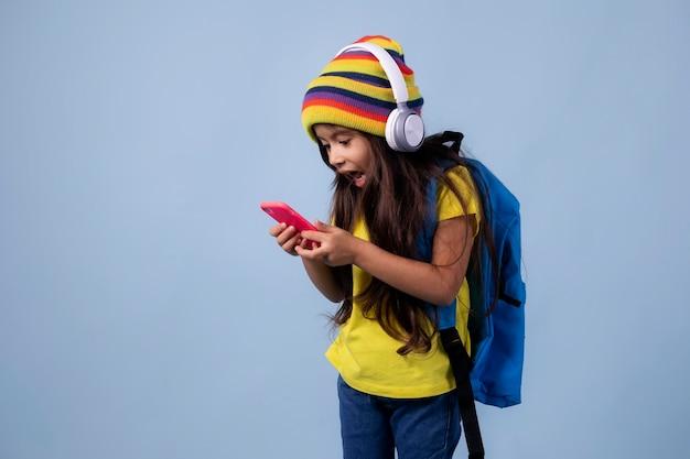 Klein aziatisch schoolmeisje dat haar telefoon controleert