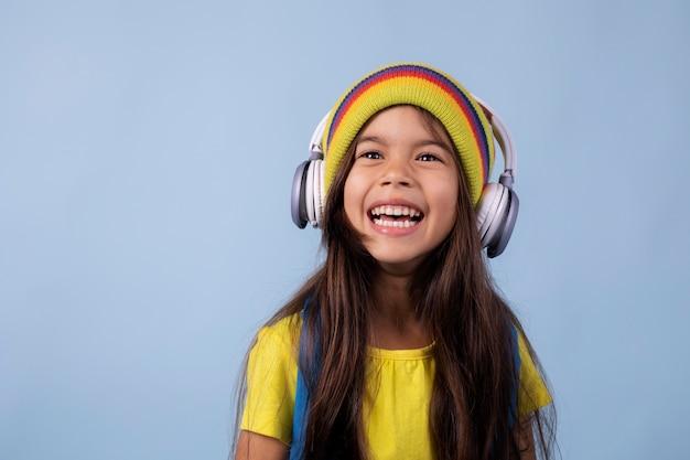 Klein aziatisch schoolmeisje dat naar muziek luistert op een koptelefoon