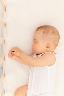 Klein babymeisje 6 maanden oud die in een wit bed, gezonde babyslaap slapen
