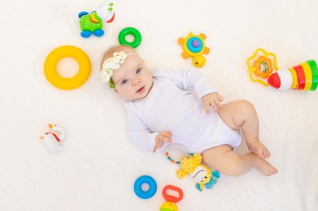 Klein babymeisje 6 maanden oud liggend op haar rug op een wit bed thuis onder speelgoed, bovenaanzicht