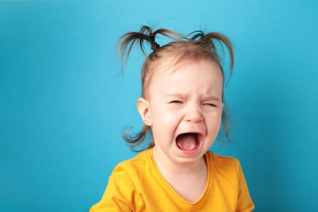 Klein babymeisje huilen geïsoleerd op blauw