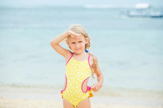 Klein babymeisje is mooi en gelukkig in een helder zwempak in de middag op een zonnig strand
