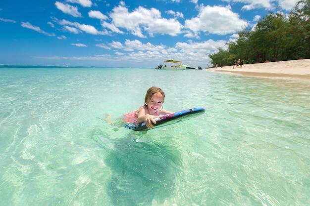 Klein babymeisje. jonge surfer met bodyboard vermaakt zich op kleine oceaangolven. actieve gezinslevensstijl