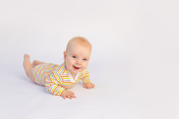 Klein babymeisje ligt op een witte geïsoleerde achtergrond in een lichte romper
