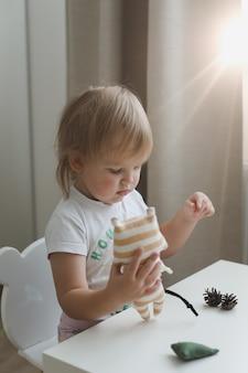 Klein babymeisje speelt met grappig klein tijgerspeelgoedsymbool van nieuw in een zonnige kinderkamer