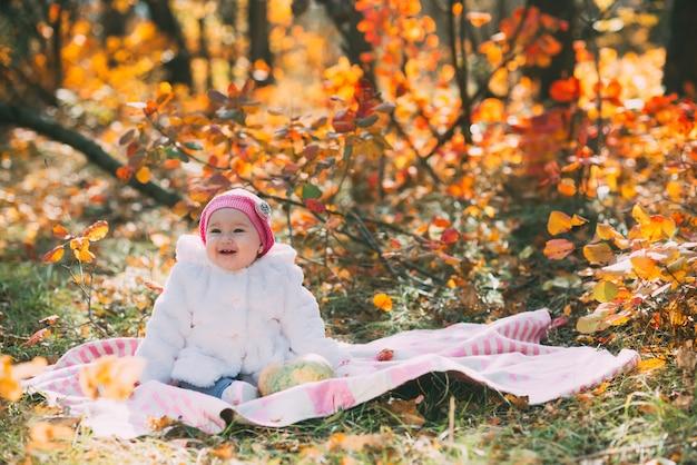 Klein babymeisje zittend op een deken in het herfstbos