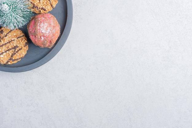 Klein bakje koekjes met een boombeeldje op marmeren ondergrond