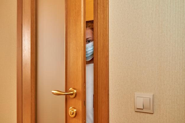 Klein bang meisje draagt een beschermend gezichtsmasker op zoek door de spleet in de deur