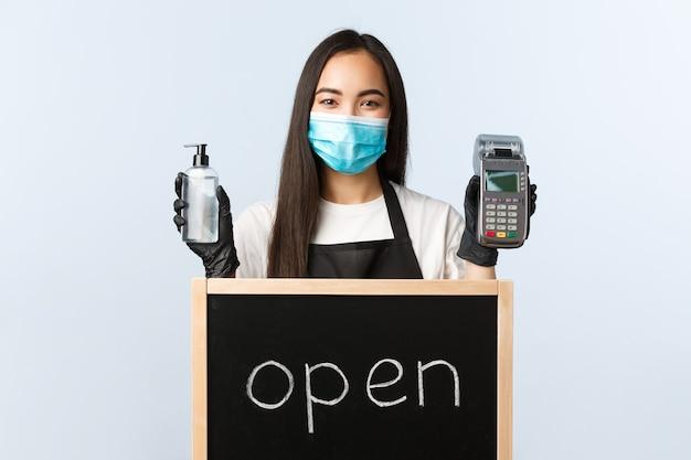 Klein bedrijf, covid-19 pandemie, preventie van virussen en contactloze bestellingen. leuke aziatische vrouwelijke barista of serveerster met we zijn open bord, met handdesinfecterend middel en betaalterminal