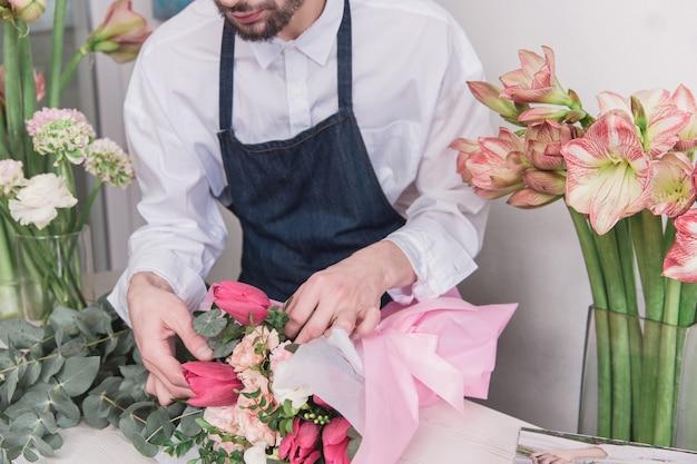 Klein bedrijf. mannelijke bloemist in bloemenwinkel. het maken van decoraties en arrangementen