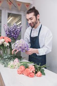 Klein bedrijf. mannelijke bloemist in bloemenwinkel.