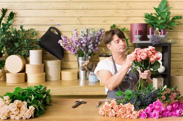 Klein bedrijf. mannelijke bloemist rozen boeket maken bij balie in bloemenwinkel. man assistent of eigenaar in bloemenwinkel, decoraties en arrangementen maken. bloemen bezorgen, orde scheppen