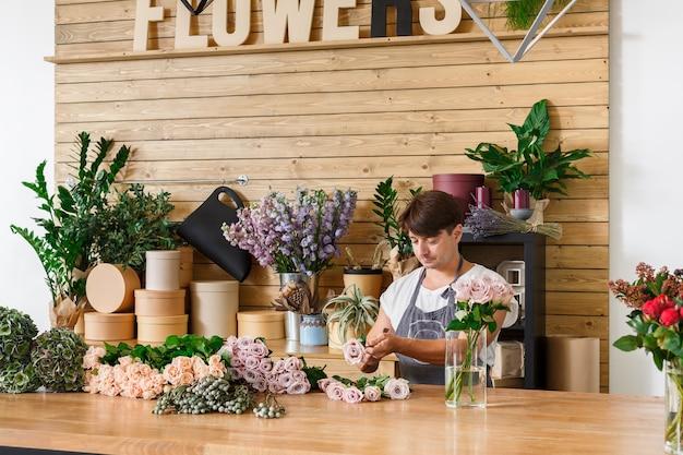Klein bedrijf. mannelijke bloemist rozen boeket maken in bloemenwinkel. assistent of eigenaar in bloemdessinatelier, maakt decoraties en arrangementen. bloemen bezorgen, orde scheppen