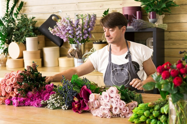 Klein bedrijf. mannelijke bloemist rozen boeket maken in bloemenwinkel. man assistent of eigenaar in bloemenwinkel, decoraties en arrangementen maken. bloemen bezorgen, orde scheppen