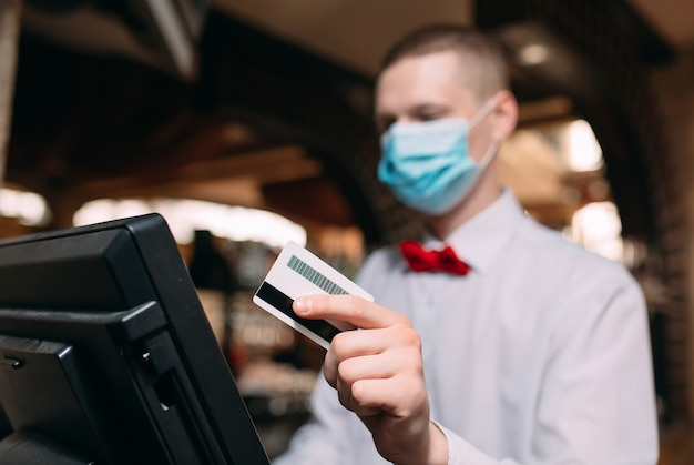 Klein bedrijf, mensen en serviceconcept. man of ober in medisch masker aan balie met kassa werken bij bar of coffeeshop.