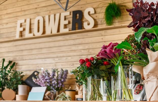 Klein bedrijf. modern bloemenwinkelinterieur. floral design studio, verkoop van decoraties en arrangementen. bloemenbezorgservice en verkoop van huisplanten in potten, houten vitrine.