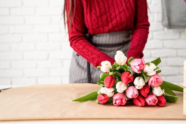 Klein bedrijf. vrouw bloemist een boeket verse kleurrijke tulpen maken