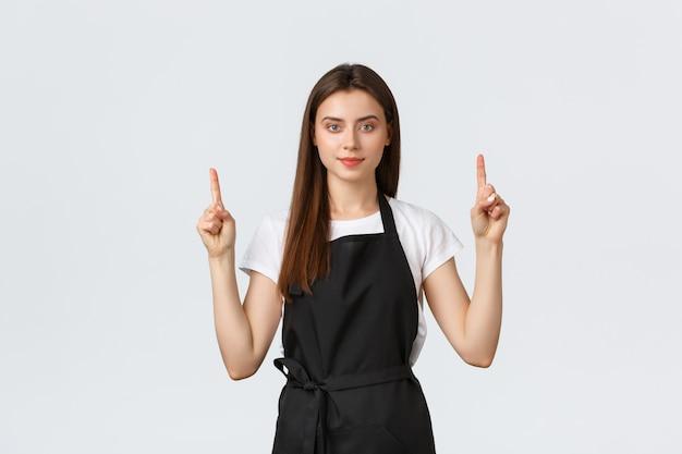 Klein bedrijf, werknemers en coffeeshop concept. handige mooie barista in zwarte schort wijzende vingers. cafe werknemer advertentie tonen. vrolijke verkoopster adviseert speciale promo