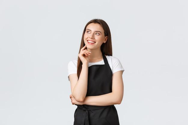 Klein bedrijf, werknemers en coffeeshopconcept. dromerige lachende mooie verkoopster in zwarte schort op zoek naar rechtsboven beeldvorming. winkelbediende of kelner die zich in restaurant bevindt.