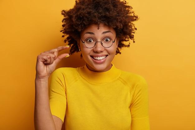 Klein beetje. mooie glimlachende vrouw meet een klein onzichtbaar object, lacht blij, draagt een ronde bril en een casual t-shirt, geïsoleerd op een gele muur, vertelt over salarisinkomen of verlaagde prijs