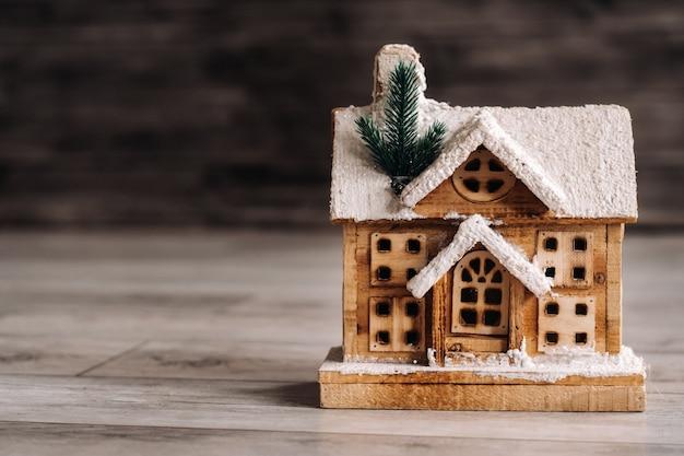 Klein besneeuwd kersthuisje op de vloer van het huis.
