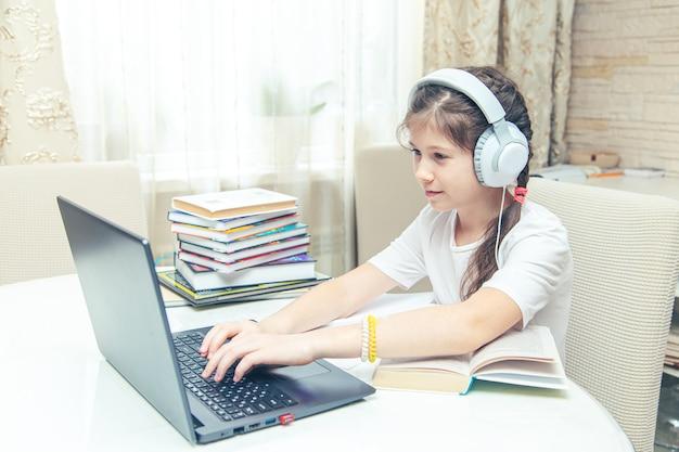 Klein blank meisje met koptelefoon kijken naar een video-tutorial op de computer. online leren op computer, thuisonderwijs concept.