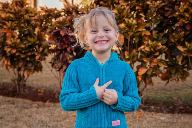 Klein blond kindmeisje glimlachend in de camera in koude trui in de tuin