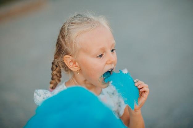Klein blond meisje dat blauwe suikerspin eet in het park.