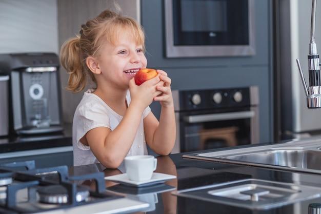 Klein blond meisje dat een appel eet in de keuken
