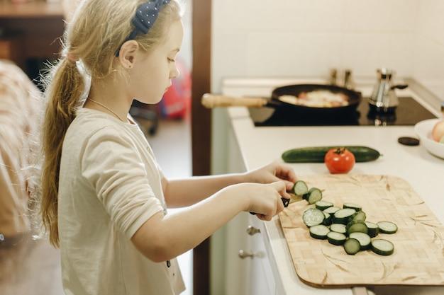 Klein blond meisje dat groenten snijdt tijdens het koken in de keuken thuis.