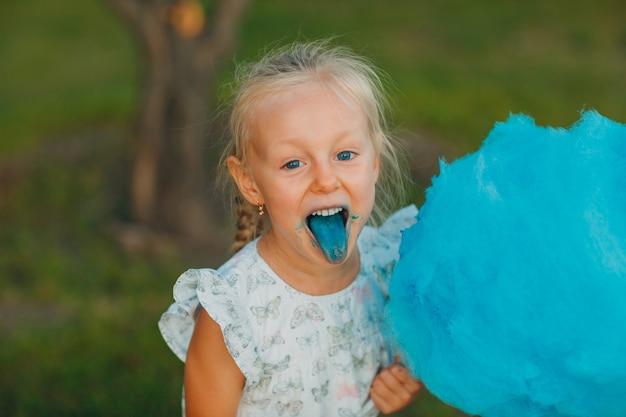 Klein blond meisje eet suikerspin en toont blauwe tong in het park.