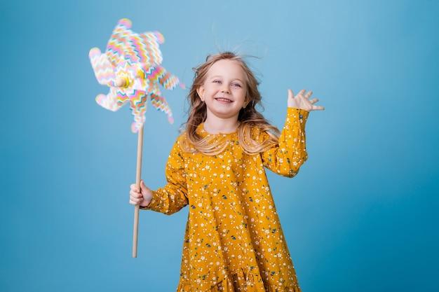 Klein blond meisje houdt een windmolen voor kinderen in haar handen