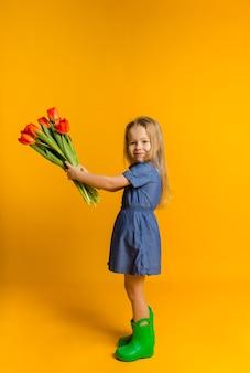 Klein blond meisje in een blauwe jurk staat zijwaarts en houdt een boeket rode tulpen op een gele muur met een kopie van de ruimte