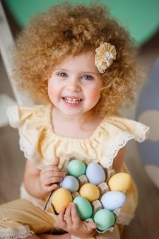 Klein blond meisje in een geel pak voor pasen