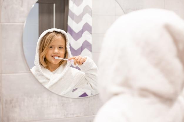Klein blond meisje in een witte badjas poetst haar tanden voor de badkamerspiegel