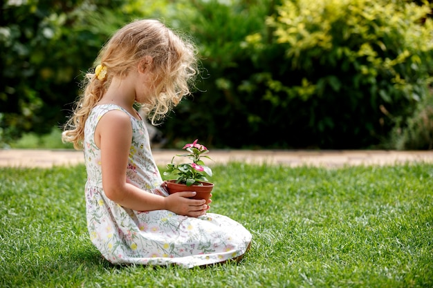 Klein blond meisje met jonge bloemplant in handen op groene achtergrond