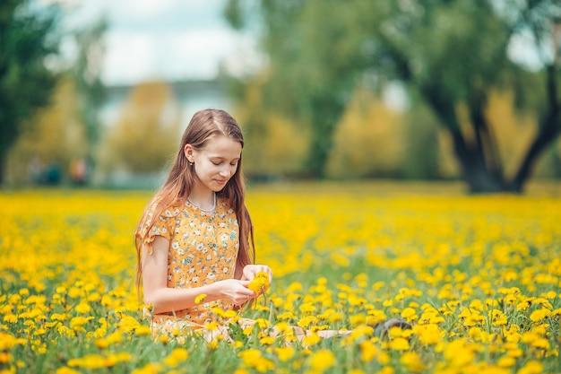 Klein blond meisje plukt bloemen in een weide vol gele paardebloemen