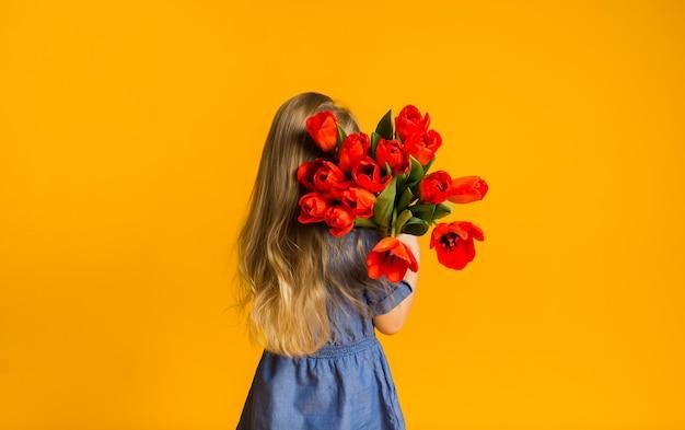 Klein blond meisje staat met haar rug naar een boeket rode tulpen op een gele muur met een kopie van de ruimte