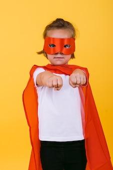 Klein blond meisje verkleed als een superheldin-superheld met een rode cape en masker, met armen in een vliegende positie, op een gele achtergrond